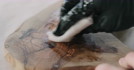 carpintero : Slow motion woodworker applying oil finish to olive wood board