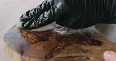 serving board : Slow motion woodworker applying oil finish to olive wood board