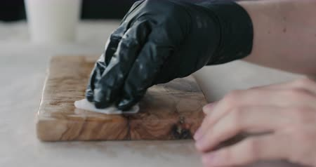 olive wood : Slow motion woodworker applying oil finish to olive wood board