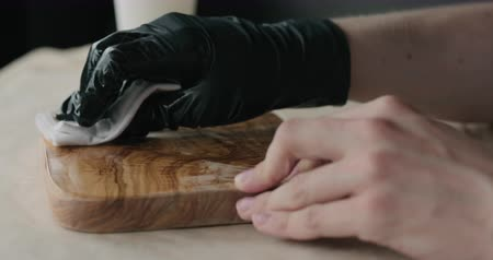 utensílio : Slow motion woodworker applying oil finish to olive wood board