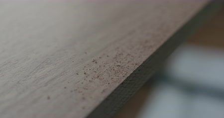 nogueira : Slow motion woodworker hand sanding walnut board with file