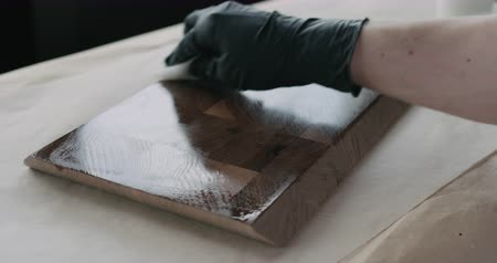 walnoot : Slow motion woodworker applying oil finish to walnut end grain wood board