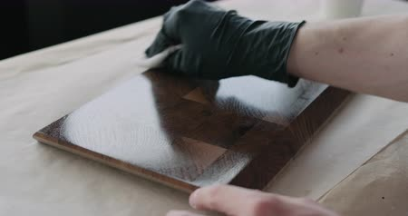 orzech : Slow motion woodworker applying oil finish to walnut end grain wood board