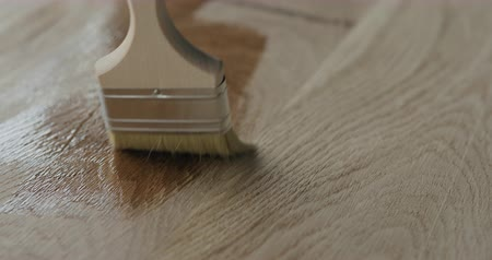 твердая древесина : Slow motion applying oil finish to oak surface with brush