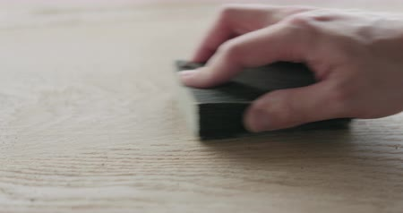 bricoleur : Slow motion closeup man hand sandig oak surface with sanding block