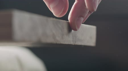nozes : Slow motion woodworker touching untreated black walnut board