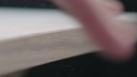 brushing : Slow motion woodworker brushing off shavings from black walnut board after sanding Stock Footage