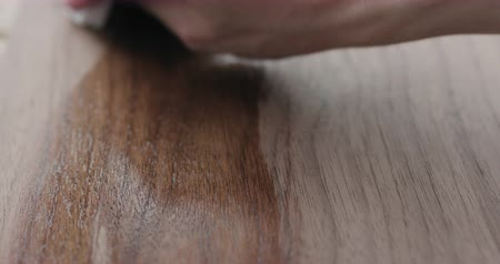 black walnut : Slow motion woodworker applying oil finish to black walnut board