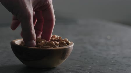 ореховая скорлупа : Slow motion man hand takes walnut kernels from wooden bowl on terrazzo countertop