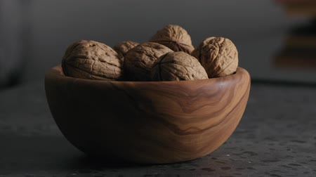 suszone owoce : Slow motion shelled walnuts falling into wooden bowl on terrazzo countertop