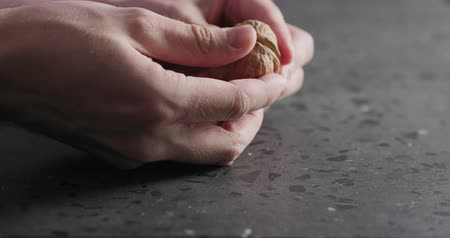 suszone owoce : Slow motion closeup man hands opens walnut Wideo