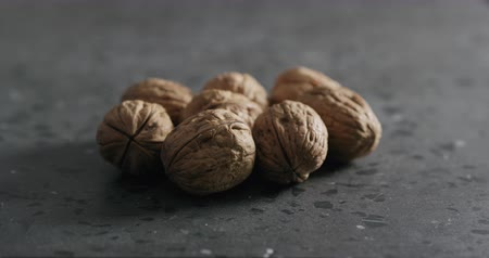 nogueira : Slow motion man hand takes walnuts from terrazzo countertop