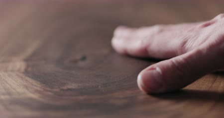 паркет : Slow motion man hand touch oil finished black walnut wood surface