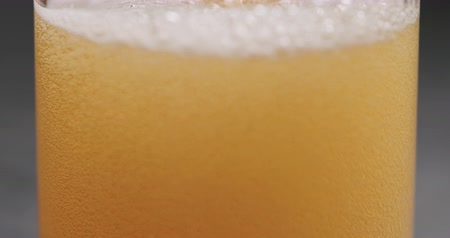focus on : Closeup slow motion pour pear cider into glass on terrazzo countertop