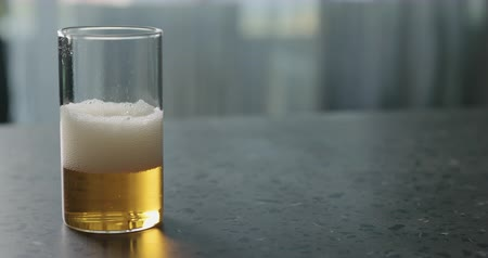 quartilho : Slow motion pear cider in glass on terrazzo countertop with copy space