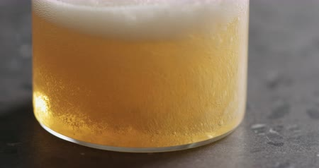 cidra : Closeup slow motion pour pear cider into glass on terrazzo countertop