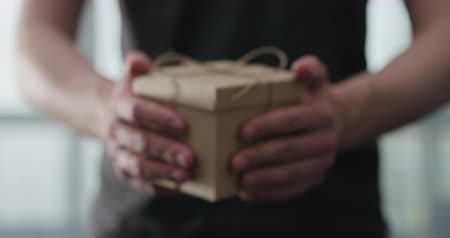 sznurek : Slow motion young man shows brown craft paper gift box Wideo