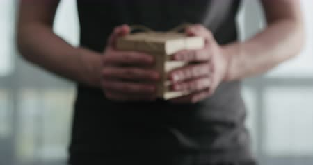 hediyeler : Slow motion young man shows brown craft paper gift box Stok Video