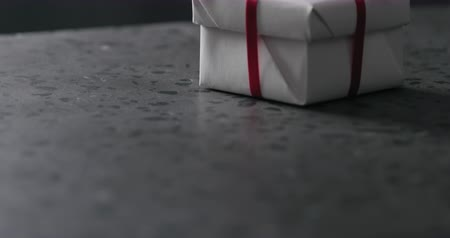 countertop : Tilt shot of white gift box with red ribbon on terrazzo countertop