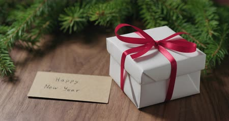 orzech : Slow motion man hand put happy new year card next to gift box with red ribbon near spruce twig on walnut table