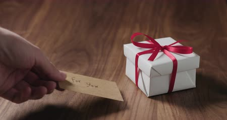 selamlar : Slow motion man hand put for you card next to white gift box on walnut table Stok Video