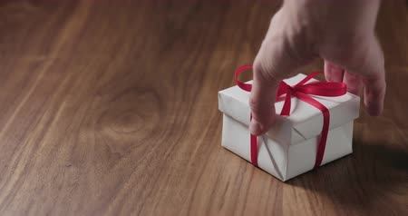 nogueira : Slow motion man hand put white gift box with red ribbon on walnut table