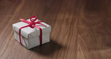 apporter : Slow motion man hand put white gift box with red ribbon on walnut table