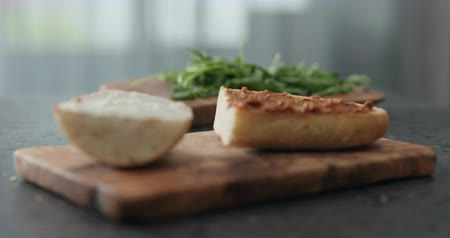 focus pull : Slow motion focus pull of ciabatta sandwich with red pesto and cream cheese on terrazzo countertop Stock Footage