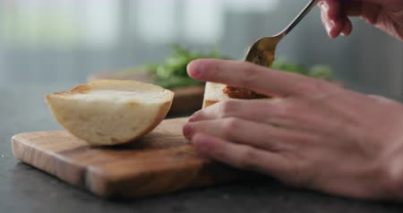 olive wood : Slow motion man spread red pesto on ciabatta slice on olive board