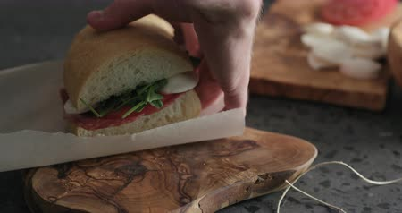salam : Slow motion man hands packing ciabatta sandwich with salami and cheese