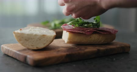 salame : Slow motion man put arugula on ciabatta slice on olive board