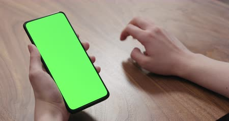 nogueira : Young woman sitting at a table and using a smartphone with vertical green screen