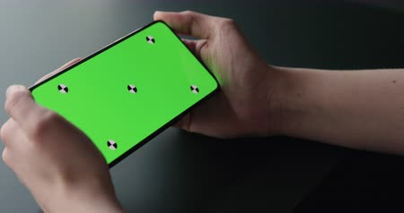 moins : Slow motion handheld shot of young woman sitting at the black table near window and holding smartphone with horizontal green screen