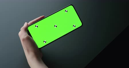 menos : Slow motion handheld shot of young woman sitting at the black table near window and holding smartphone with horizontal green screen