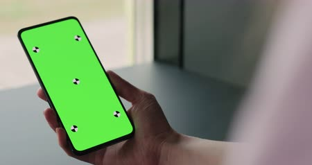 menos : Slow motion handheld shot of young woman sitting at the black table near window and holding smartphone with vertical green screen