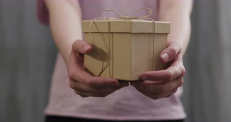 sznurek : Slow motion young woman stand and show brown gift box with twine bow Wideo