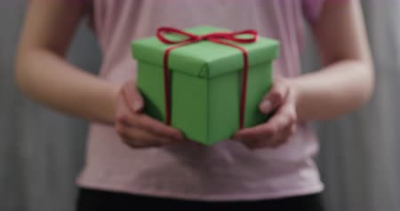 ajándékok : Slow motion young woman stand and show green gift box with red ribbon bow