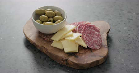 antipasti : Slow motion handheld shot of green olives, cheese and salami on olive wood board