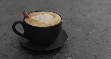 italian coffee : Slow motion adding marshmallow into cappuccino in black cup on terrazzo countertop