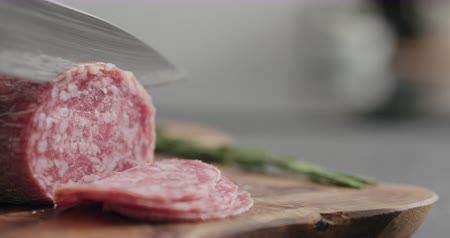 lanches : Slow motion man slicing salame sausage on olive wood board Stock Footage