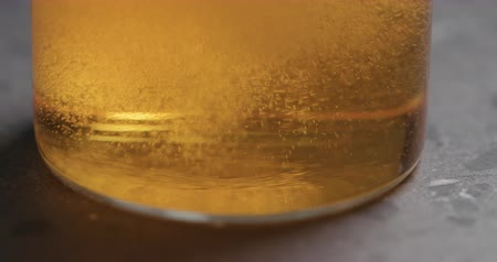 amargo : Closeup slow motion pour pear cider into glass on terrazzo countertop