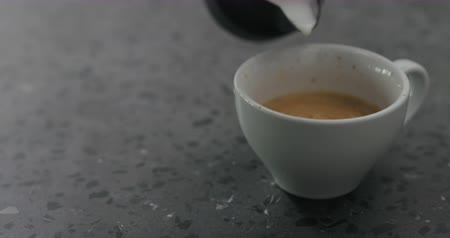 betoniarka : Slow motion pouring steamed milk into cappuccino in white cup on terrazzo countertop
