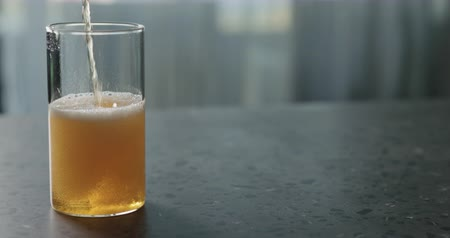 amargo : Slow motion pour pear cider into glass on terrazzo countertop with copy space