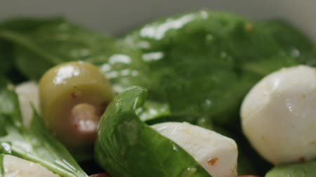 スターター : Slow motion handheld shot of salad with mozzarella, spinach and cherry tomatoes in white bowl 動画素材