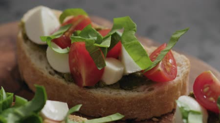 bread pan : Slow motion handheld shot of bruschetta with cherry tomatoes, mozzarella and spinach