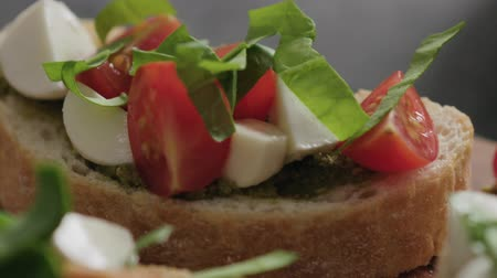 olive wood : Slow motion handheld shot of bruschetta with cherry tomatoes, mozzarella and spinach