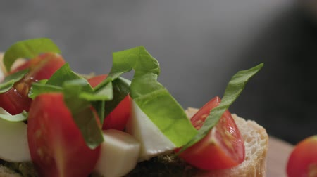 tomates cereja : Slow motion handheld shot of bruschetta with cherry tomatoes, mozzarella and spinach