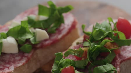 picado : Slow motion handheld shot of bruschetta with salame, cherry tomatoes, mozzarella and spinach Stock Footage