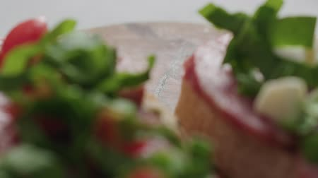 bread pan : Slow motion handheld shot of bruschetta with salame, cherry tomatoes, mozzarella and spinach Stock Footage