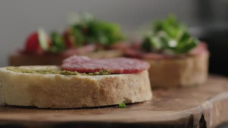 olive wood : Slow motion closeup man hands making bruschetta with pesto and salame